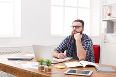 De peinzende jonge zakenman neemt nota's in modern wit bureau Stock Fotografie