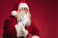 De peinzende Kerstman wat betreft baard en kin Royalty-vrije Stock Afbeeldingen