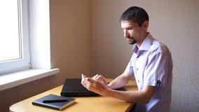 De peinzende mens schrijft berichten op telefoon stock video