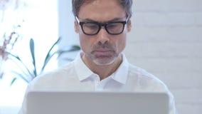 De peinzende midden oude mens die en aan laptop denken werken, ziet dicht omhoog op uit stock footage