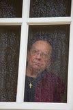 De peinzende oudste kijkt droevig van een venster Royalty-vrije Stock Afbeelding