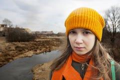 De peinzende Tiener in sinaasappel knitten hoed en sjaaltribune alleen dichtbij het geschroeide gebied royalty-vrije stock foto's