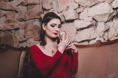 De peinzende vrouw die in avondjurk een spiegel houden, bekijkt zorgvuldig haar gezicht met heldere make-up rokerige ogen, rode l Stock Foto