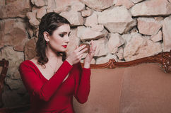 De peinzende vrouw die in avondjurk een spiegel houden, bekijkt zorgvuldig haar gezicht met heldere make-up rokerige ogen, rode l Royalty-vrije Stock Fotografie
