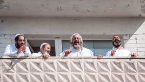 De pelgrims van Hasidi op het balkon van het high-rise gebouw hebben pret vierend de vakantie van rosh-Ha-Shana stock afbeelding