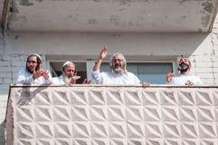 De pelgrims van Hasidi op het balkon van het high-rise gebouw hebben pret vierend de vakantie van rosh-Ha-Shana royalty-vrije stock afbeelding