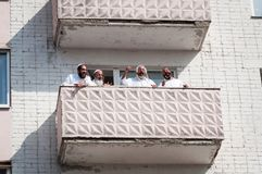 De pelgrims van Hasidi op het balkon van het high-rise gebouw hebben pret vierend de vakantie van rosh-Ha-Shana royalty-vrije stock afbeeldingen