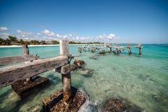 De pelikanen zitten op een oude verlaten pijler Het Strand van Xpuha, Mexico stock foto