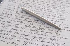 De Pen die van het roestvrij staal op Geschreven Pagina leggen Stock Foto's