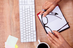 De pen en het oogglazen van de onderneemsterholding Stock Afbeeldingen