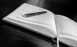 De pen ligt op open blanco pagina's van een organisator stock afbeelding