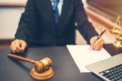 De pen van de advocaatholding met het schrijven op Witboek en houten hamer stock foto's