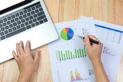 De pen van de bedrijfsvrouwenholding het in hand werken met financiële document grafieken en laptop computer royalty-vrije stock fotografie
