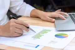 De pen van de bedrijfsvrouwenholding het in hand werken met financiële document grafieken en laptop computer royalty-vrije stock foto's