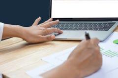 De pen van de bedrijfsvrouwenholding het in hand werken met financiële document grafieken en laptop computer royalty-vrije stock afbeelding