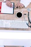 De pen van de artsenholding op bureau Stock Afbeeldingen