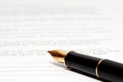 De pen van de inkt op het document Stock Afbeeldingen