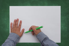 De pen van de kindholding op leeg blad van document Stock Afbeelding