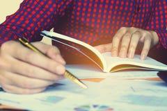De pen van de mensenholding en het denken over kosten thuis bureau Royalty-vrije Stock Afbeelding