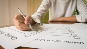 de pen van de handholding op het document van de kwaliteitscontrole en het formaat voor het invullen van informatie in bedrijfsco Stock Foto
