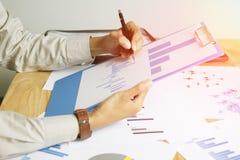 De pen van de zakenlieden in hand holding het schrijven rapportgrafiek op het bureau, die voor succes streven Stock Foto's