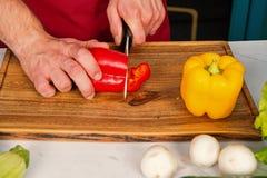 De peper van de handplak met ceramisch mes Groenten worden die die op houten scherpe raad worden gesneden Voedsel voorbereiding e stock afbeelding