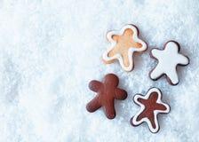 De peperkoekmensen van Kerstmis op sneeuw Stock Foto