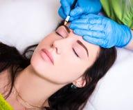 De permanente wenkbrauw maakt omhoog - schoonheidsspecialist die vrouw voor proce voorbereiden stock foto