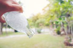 De personen overhandigen het houden van een fles water koel ijs die het poring uit binnen stock fotografie