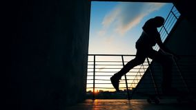 De persoon berijdt een raad op een zonsondergangachtergrond, langzame motie stock footage