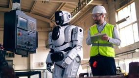 De persoon controleert werkende robot, die zich in een fabrieksruimte bevinden stock footage