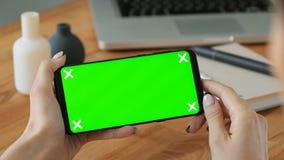 De persoon die cellphone gebruiken met greenscreen ter beschikking vertoning stock videobeelden