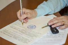 de persoon die het document van aankoop en verkoop van de auto ondertekenen stock foto