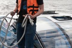 De persoon in een reddingsvest houdt ter beschikking een shvartovochny kabel Stock Afbeelding