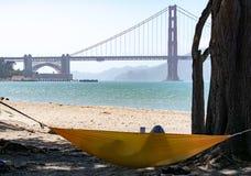 De persoon legt in hangmat terwijl het lezen van boek met het Golden Gate B royalty-vrije stock afbeelding