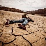 De persoon legt op de droge grond Stock Afbeelding