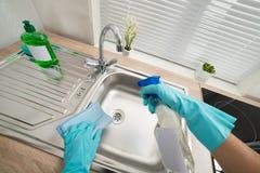 De persoon overhandigt schoonmakende keukengootsteen stock foto's
