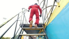 De persoon in rood kostuum die boven naar de aërodynamische buis gaan stock videobeelden
