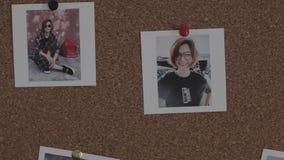 De persoon speldt twee foto's binnen van jonge vrouw op cork raad stock footage