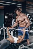 De persoonlijke trainer die een jonge vrouw helpen heft een barbell op terwijl het uitwerken in een gymnastiek royalty-vrije stock fotografie