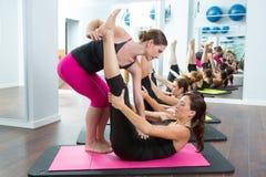 De persoonlijke trainer die van Pilates vrouwen helpt Stock Afbeeldingen
