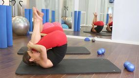 De persoonlijke trainer van aerobics pilates vrouwen met leerling op een rij bij gymnastiek stock footage