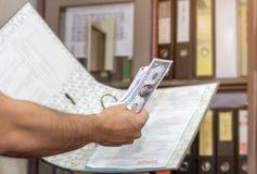 De persoonshand keurt geldsteekpenning van corrupt bouwproject goed, Royalty-vrije Stock Foto's