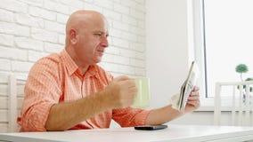 De persoonszitting op de Lijst ontspande gelezen Krant en drinkt een Kop met Koffie stock video