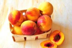 De perziken zijn in een kleine mand Stock Afbeeldingen
