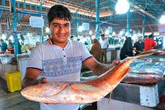 De Perzische mens houdt een grote vis in de markthal Royalty-vrije Stock Foto