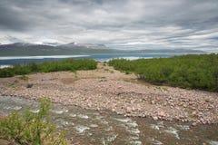 De Pessijoki-rivier die in Meer Tornetrask stromen stock afbeeldingen