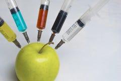 De pesticiden, de nitraten, de fungiciden en andere chemische producten worden ingespoten in een groene appel met een spuit Sluit royalty-vrije stock foto