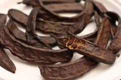 De peulen en de zaden van het johannesbrood stock afbeeldingen