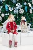 de peuter van het babymeisje met blauwe ogen in rode kledingszitting door Nieuwjaarboom dichtbij hertenstuk speelgoed Royalty-vrije Stock Afbeeldingen